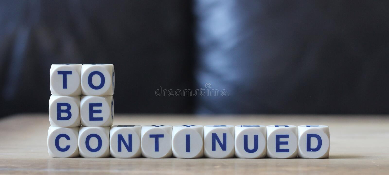 To be continued. Letters cube wordings on wood table stock image