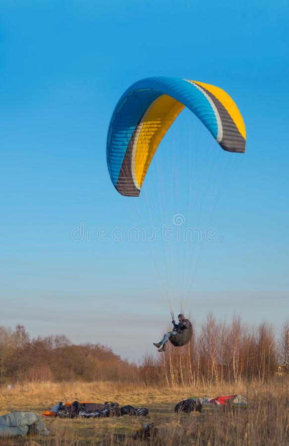 To fly on a paraglider, to be engaged in sports on a motor paraglider, paragliders are fond of flights. To be engaged in sports on a motor paraglider, to fly on stock photography