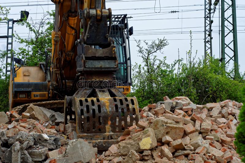 To build something you need something to break. Excavator breaks and destroys the old building in order to build a new one stock images