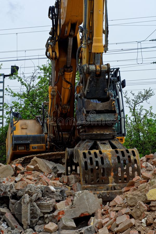 To build something you need something to break. Excavator breaks and destroys the old building in order to build a new one royalty free stock photo