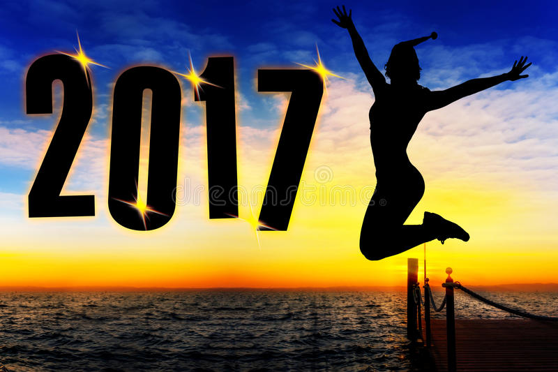 To celebrate the New Year 2017 silhouette of young woman. Jumping on the beach stock photos