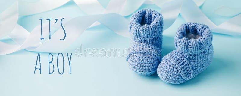 To chłopiec. Niebieskie buty dziane dla noworodków na niebieskim tle, Minimal baby shower, tło noworodka, kopia zdjęcia royalty free
