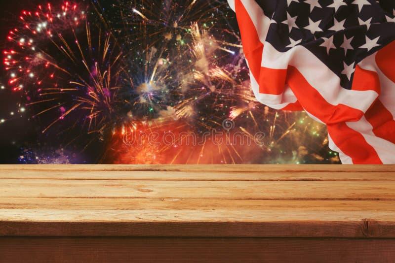 4to del fondo de julio Tabla de madera sobre los fuegos artificiales y bandera de los E.E.U.U. Celebración del Día de la Independ fotografía de archivo