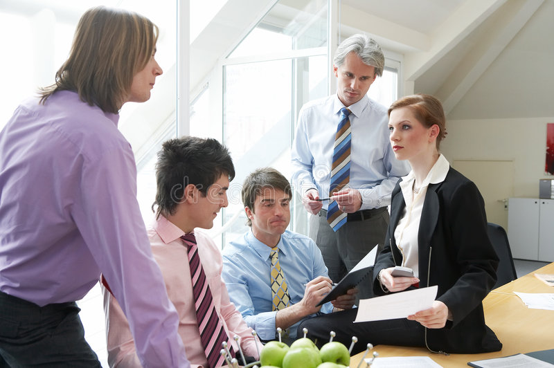 To dispute. Five businesspeople are discussing something on a meeting