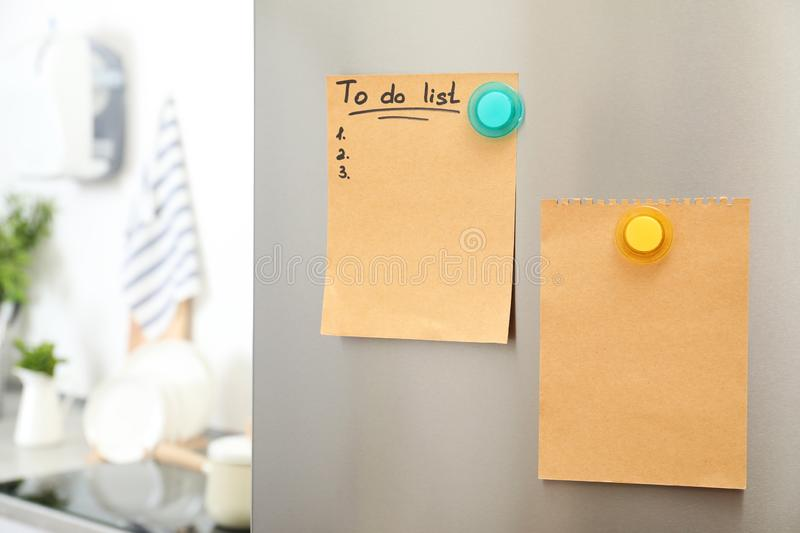 To do list and empty sheet of paper with magnets on refrigerator door in kitchen. Space for text stock photo
