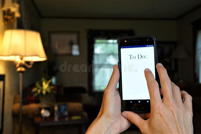 To Do list on smartphone. Electronic to do listing of items luminescent on cell phone screen.  Woman`s hands hold and prepare to tap out information, lamp shines stock image
