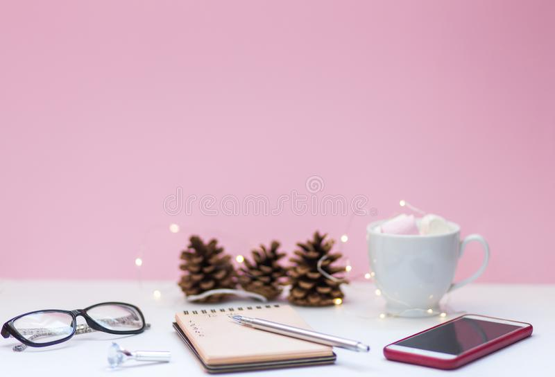 To-do list on the withe table. Notebook with handwritten to-do list, cup of coffee, smartphone and glasses on the white desk on the pink background for text stock photography