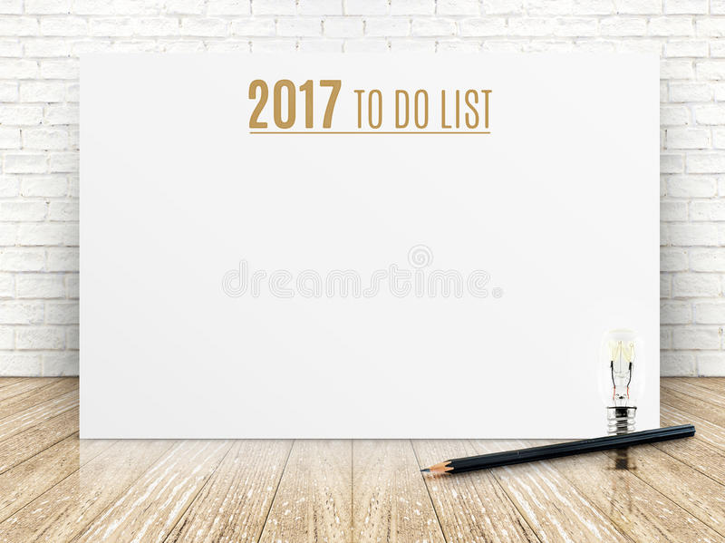 2017 To do list year text on white paper poster with black pencil and lightbulb on wood plank floor and white brick royalty free stock image