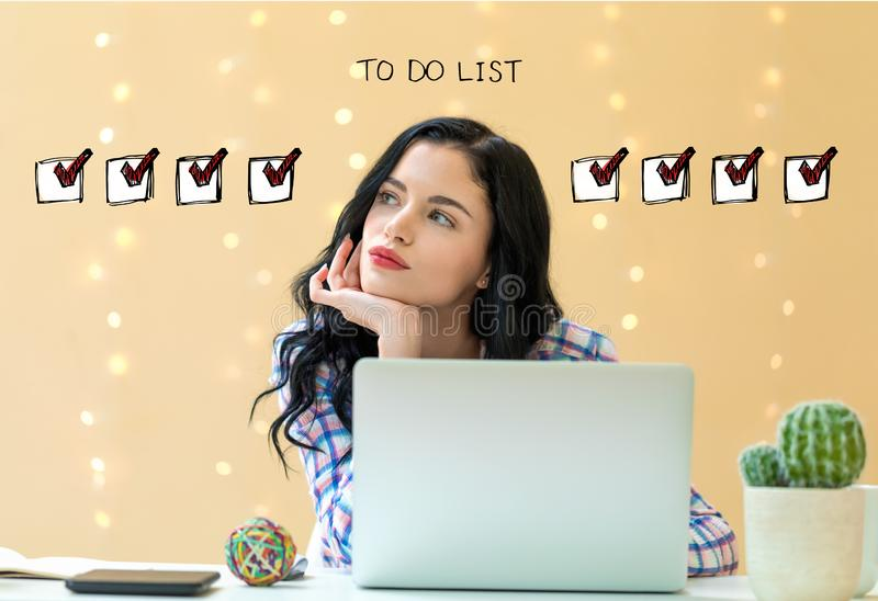 To do list with young woman. Using a laptop stock photos