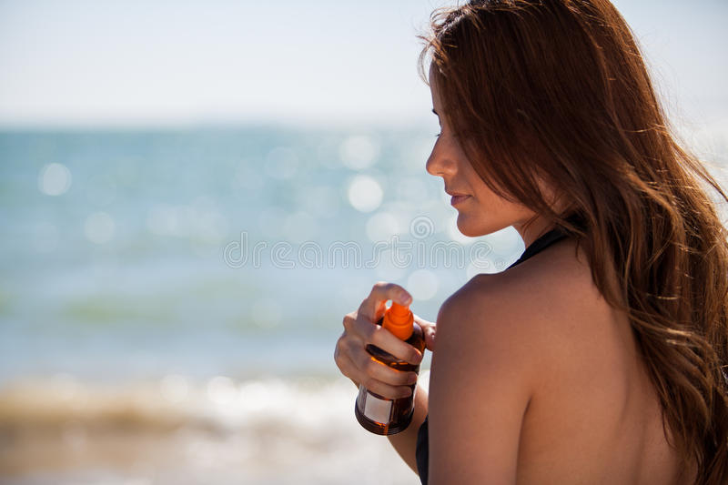 About to get a suntan. Brunette putting on some tanning lotion on her shoulder royalty free stock photo