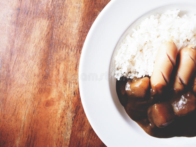 To jest kare raisu curry nad ryż w bielu talerzu nad drewniany zdjęcie stock