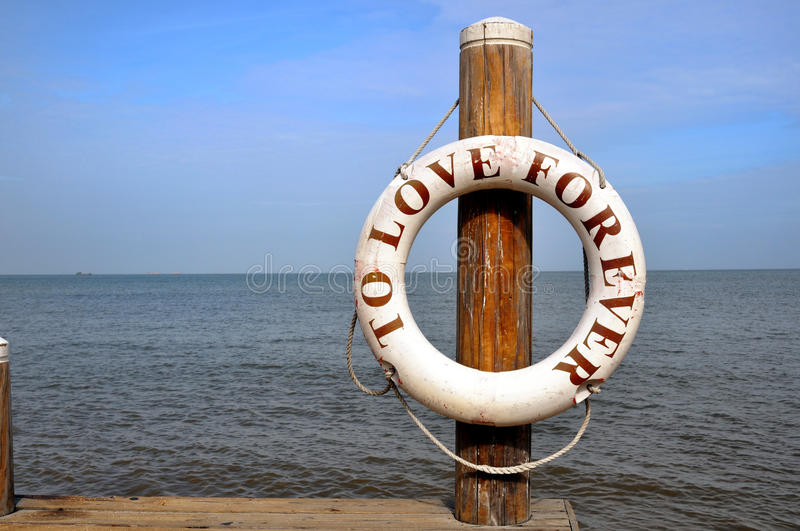 To love for ever. A life buoy writen to love for ever beside beach royalty free stock image