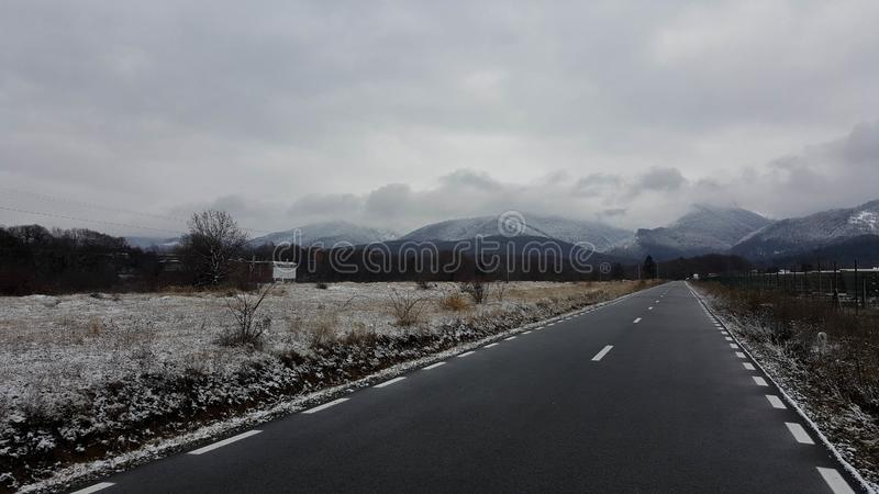 To the mountains in wintertime. A desolate winter landscape. A road leading to the mountains in the background. The entire landscape is covered in scarce snow royalty free stock photography