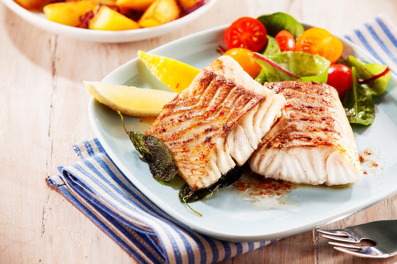 To portions of fresh grilled pollock. Or coalfish served with colorful salad and slices of lemon, close up high angle view stock photos