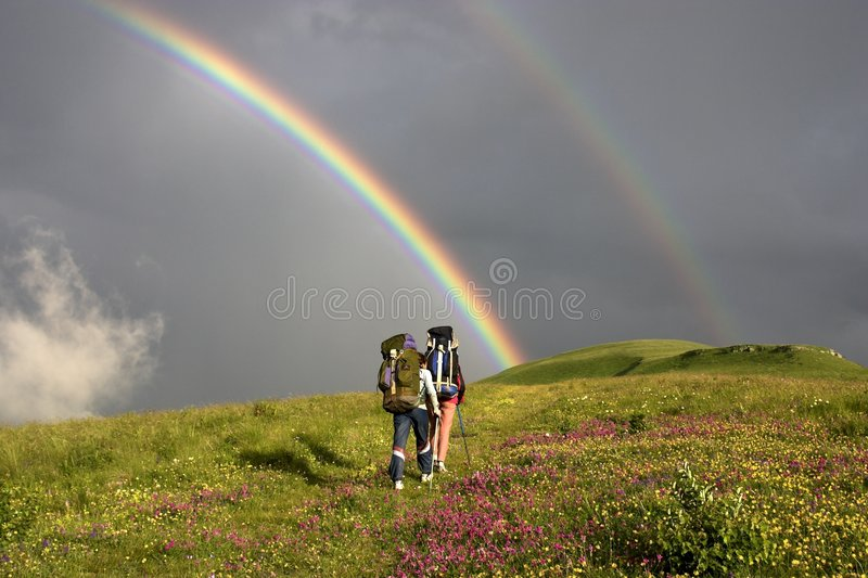 To the raibow. Two tourists with backpacks hike towards the rainbow royalty free stock photography