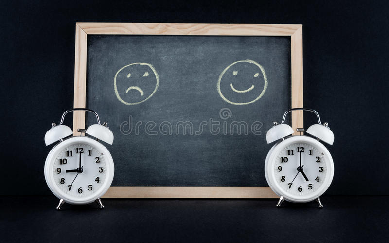9 to 5 sad corporate working hours concept. Two vintage alarm clocks showing 9 and 5 o'clock with happy and sad smileys on chalkboard on black background. Nine stock photos