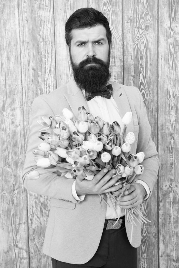 To say I love you. Womens day. Flower for March 8. Spring gift. Bearded man hipster with flowers. Bearded man with tulip. Bouquet. Love date. international royalty free stock photo