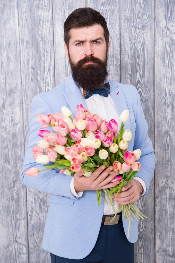 To say I love you. Womens day. Flower for March 8. Spring gift. Bearded man hipster with flowers. Bearded man with tulip. Bouquet. Love date. international stock images