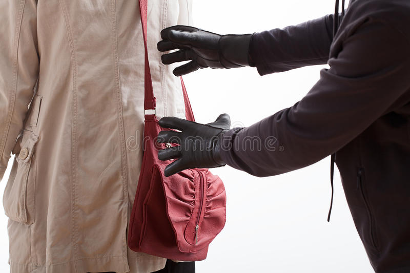 About to steal. A thief in leather gloves about to steal a red bag stock photo