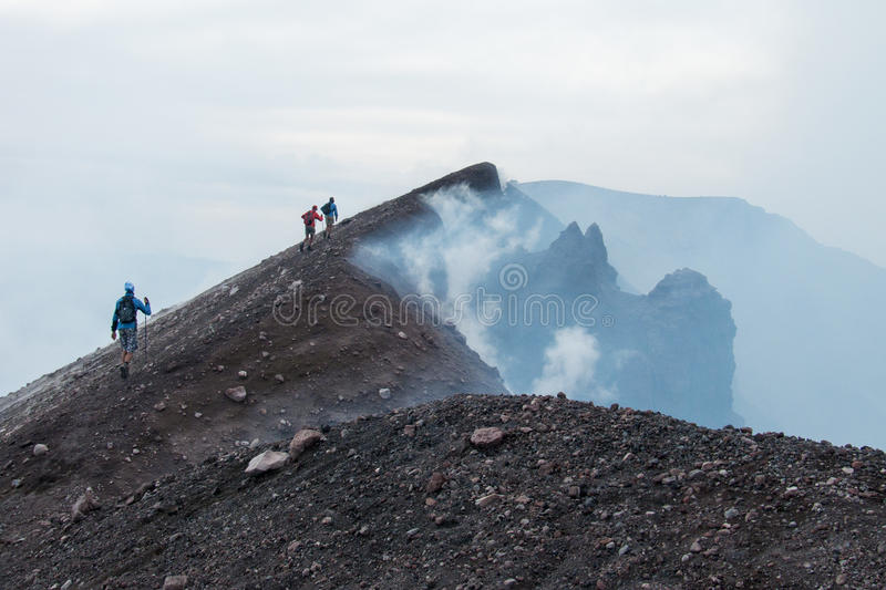 To the top of the Etna volcano. Hikers go on the lava fields to the summit of Etna