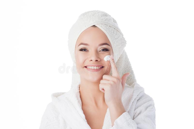 To use the cream after a shower. Portrait of a young attractive woman in a Bathrobe and a towel on her head. stock photos