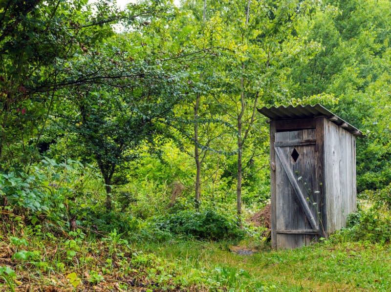 Toalete de madeira velho na vila foto de stock