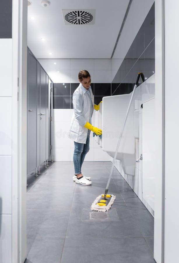 Toalete dos mictórios da limpeza da mulher do guarda de serviço em público fotos de stock royalty free