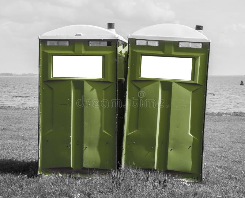 Toalete móvel verde em uma praia preto e branco fotografia de stock royalty free