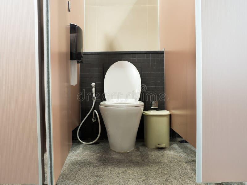 Toalete nivelado do abertura da porta do toalete e o branco com baldes do lixo e caixa do papel higiênico fotografia de stock