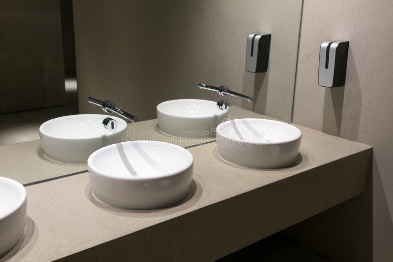 Toalete público com as bacias de lavagem modernas fotografia de stock