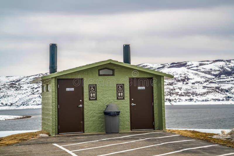 Toalete público unisex contra a montanha nevado do lago e o céu nebuloso no inverno imagem de stock