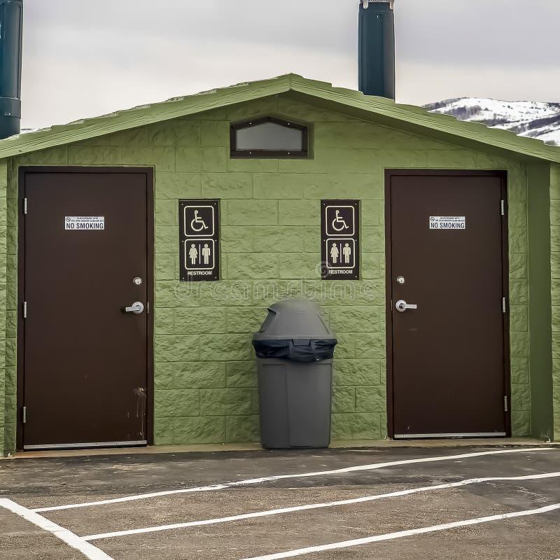 Toalete público unisex do quadrado contra a montanha nevado do lago e o céu nebuloso no inverno imagens de stock royalty free