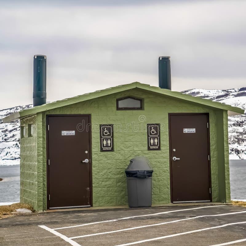 Toalete público unisex do quadro quadrado contra a montanha nevado do lago e o céu nebuloso no inverno fotos de stock