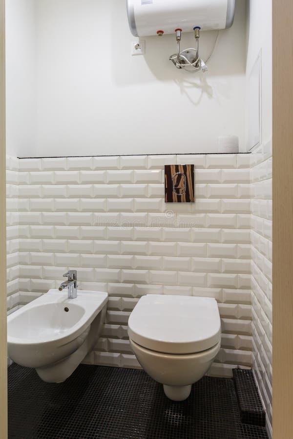 Toalett och detalj av en h?rnduschbid? med tillbeh?ret f?r v?ggmonteringsdusch arkivfoton