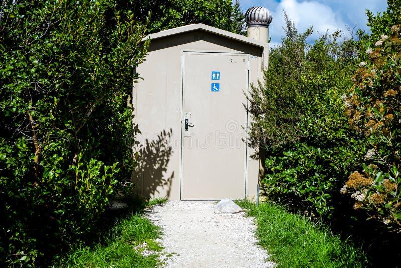 Toalett på WC:s toalett i bergsledet i form av ett trästuga nära en landskapsväg och höga träd på båda sidor royaltyfri bild