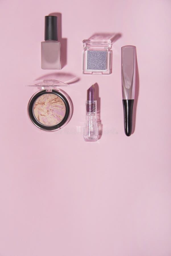 Toalettartikel på rosa bakgrund Läppstift rouge, spikar färg- och ögonskugga royaltyfri foto