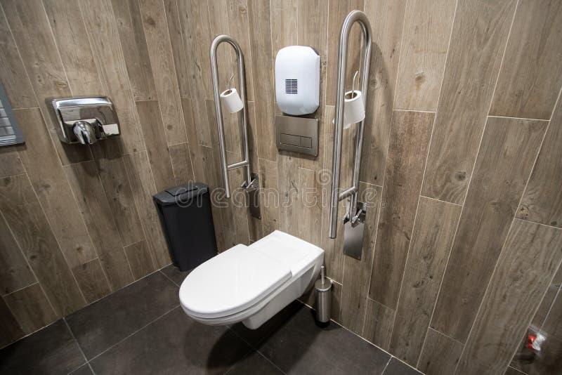 Toaletten för åldring av inaktiverar folk med ledstången på sidan arkivbilder