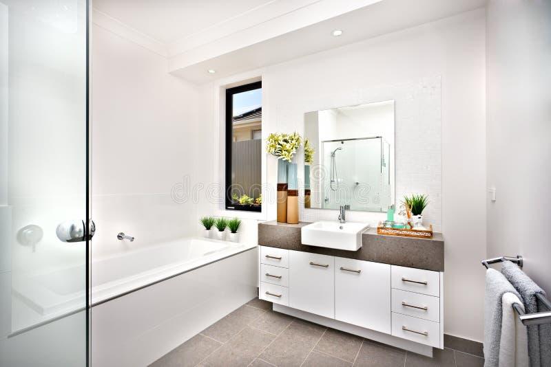Toaletten med ett bad badar bredvid ett f?nster och ett klapp arkivbilder