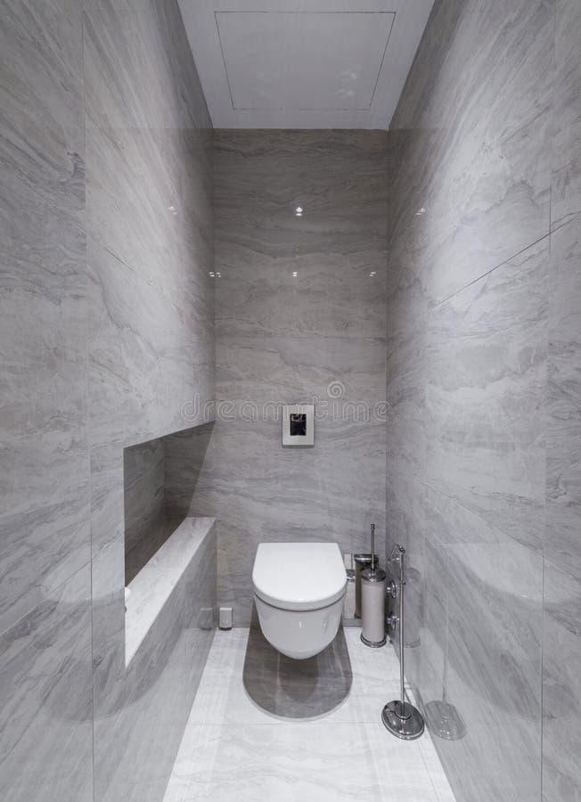 Toaletten som är inre med, marmorerar väggar arkivbild