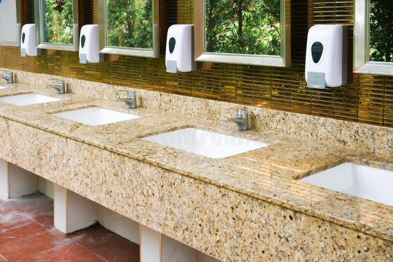 Toalettluckor invändigt i toaletten med tvätthänder och spegelgolv, ren toalett royaltyfri bild