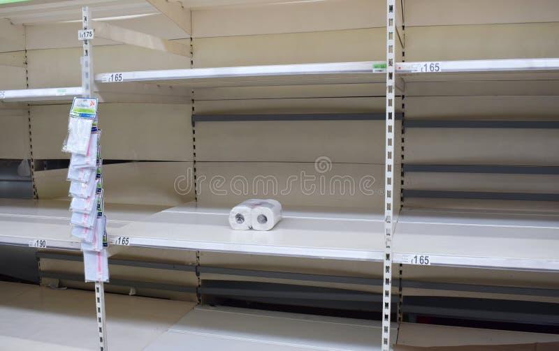 Toalettpapper Stormarknadshyllorna i Storbritannien är tomma när folk drabbas av panik genom att köpa loo roll-/toalettpapper på  royaltyfria foton