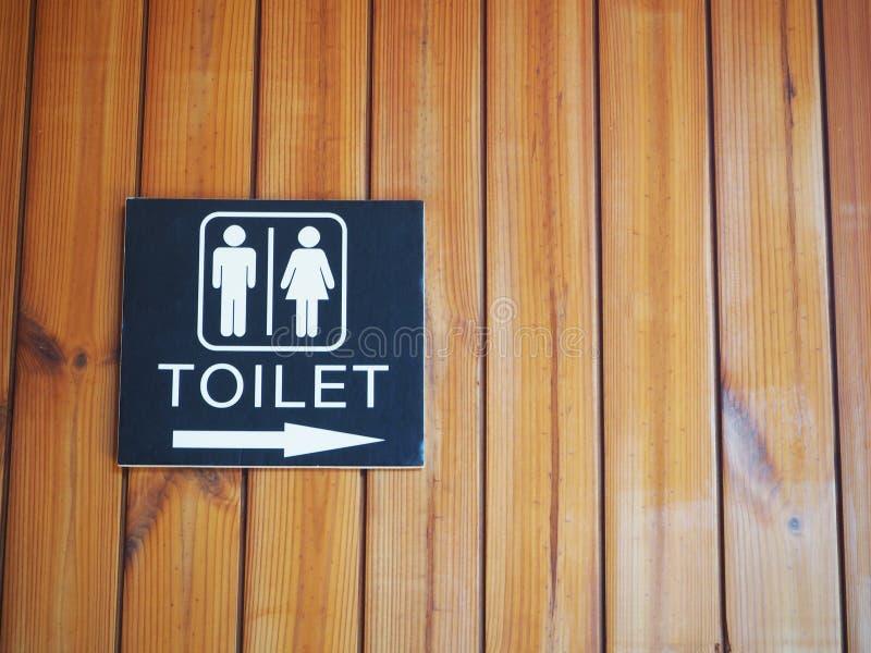 Toaletttecken med wood bakgrund arkivfoto