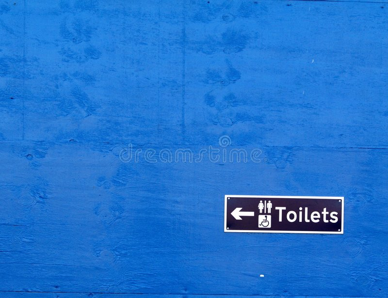 toalety szyldowa niebieski mur obrazy stock