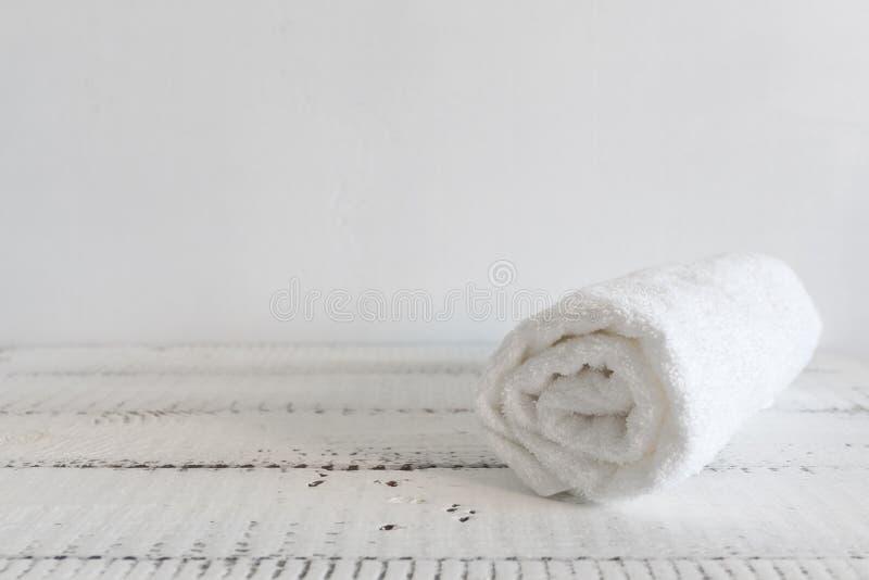 Toalha branca dobrada em uma tabela de madeira branca Termas e bem-estar, matéria têxtil de terry do algodão tema ecológico imagens de stock