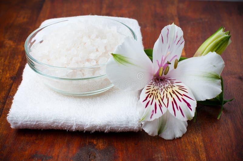 Toalha branca, sal aromático e flor