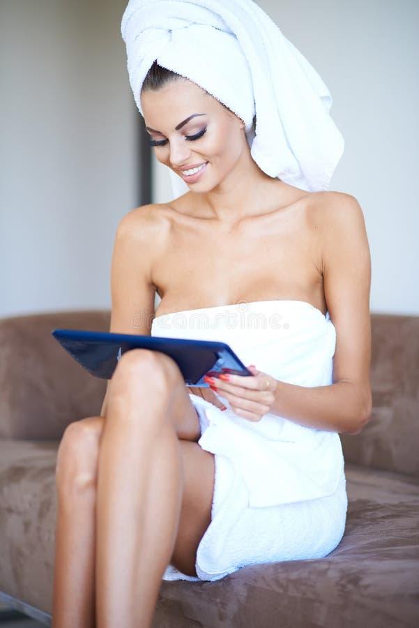 Toalha de banho da mulher e tablet pc vestindo da utilização imagens de stock royalty free