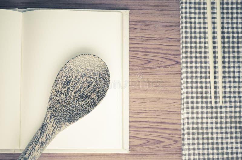 Toalha de cozinha com a colher no fundo de madeira fotografia de stock royalty free