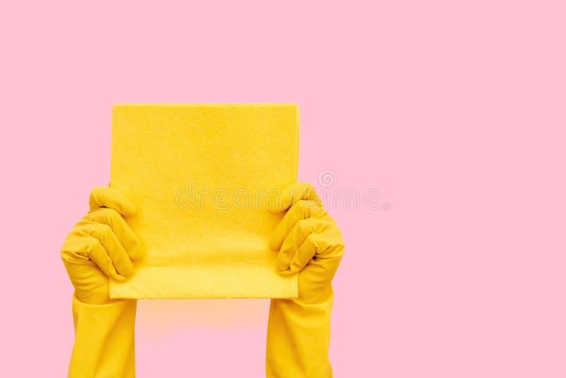 Toalha de limpeza amarela da terra arrendada da mulher em suas mãos foto de stock