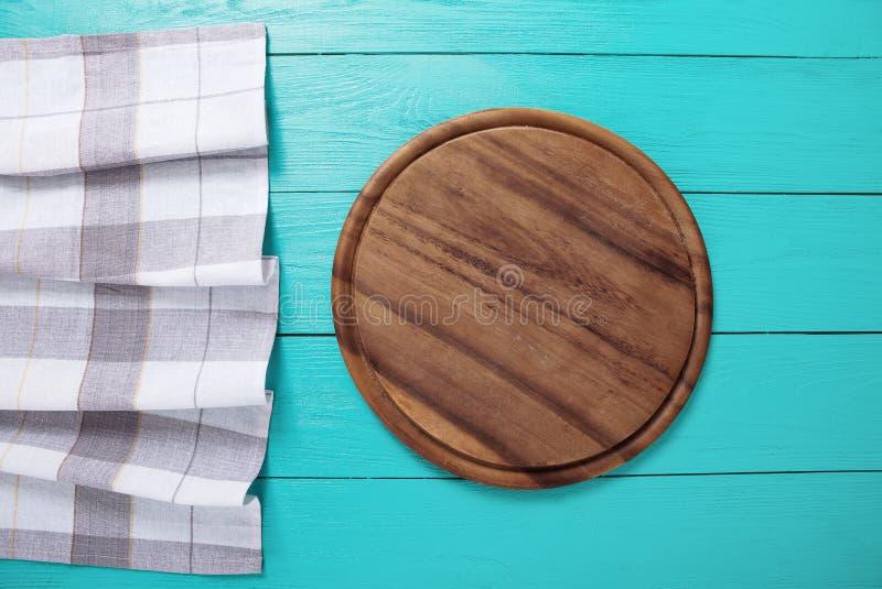 Toalha de mesa da manta, placa de corte marrom para a pizza na tabela de madeira azul Fundo de madeira Vista superior e zombaria  imagens de stock royalty free