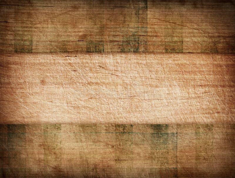 Toalha de mesa listrada do Grunge na placa de corte de madeira fotografia de stock